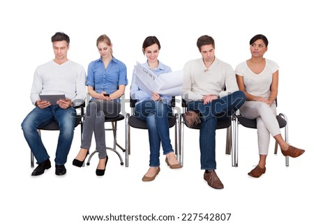 Full length of businesspeople doing various activities while sitting on chairs against white background - stock photo