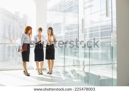Full-length of businesswomen discussing in office - stock photo