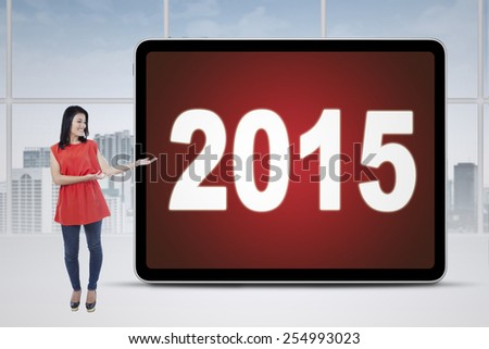 Full length of casual businesswoman standing in the office while showing numbers 2015 on a board - stock photo