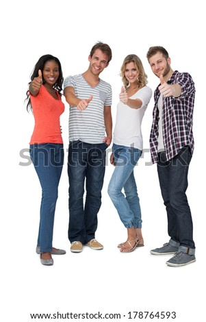 Full length of casually dressed young people gesturing thumbs up over white background - stock photo