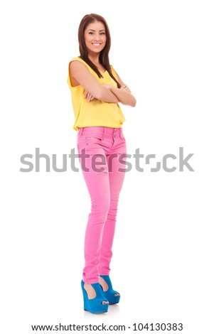 Full length of casually dressed young woman standing with hands folded - stock photo