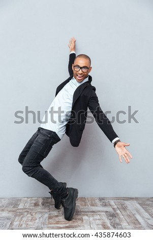 Full length of cheerful african american young man in glasses dancing - stock photo