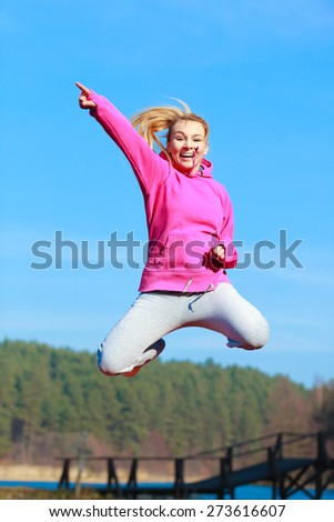 Full length of cheerful woman teenage girl in pink tracksuit jumping high showing pointing at something outdoor. Healthy active lifestyle. - stock photo