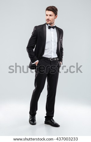 Full length of confident attractive young man in tuxedo standing over white background - stock photo