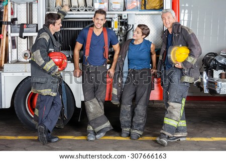 Full length of confident firefighters leaning on truck at fire station - stock photo