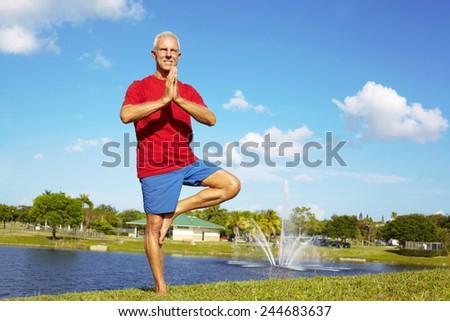 Full length of confident senior man practicing tree yoga pose at lakeshore - stock photo