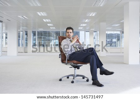 Full length of confident young businessman on chair in empty office space - stock photo