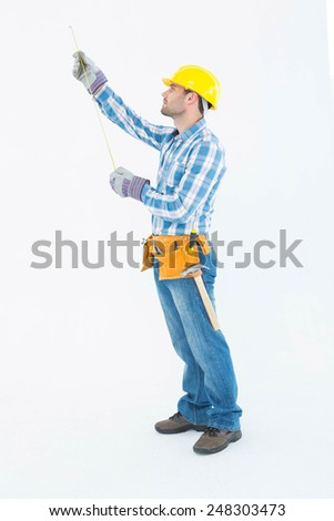 Full length of construction worker using measure tape against white background - stock photo
