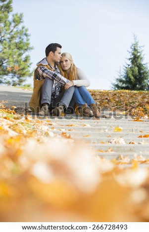 Full length of couple sitting on steps in park - stock photo