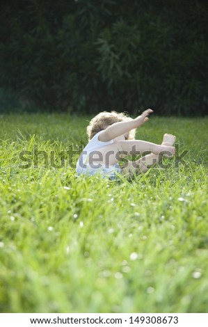 Full length of cute baby girl toppling on grass in lawn - stock photo