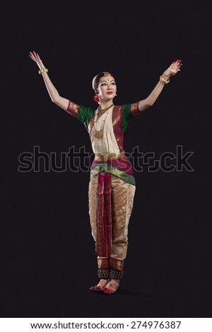 Full length of dancer with arms raised performing Bharatanatyam against black background - stock photo