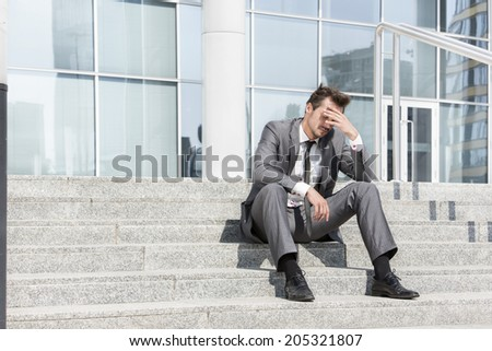 Full length of depressed businessman sitting on steps outside office - stock photo