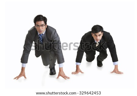 Full length of determined businessmen getting ready for race against white background - stock photo
