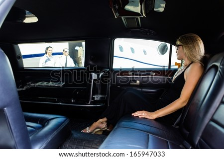 Full length of elegant woman in limousine at airport terminal - stock photo
