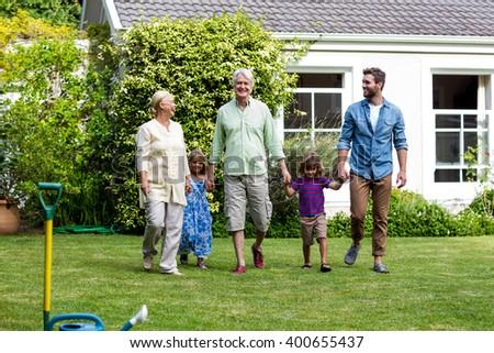 Full length of family walking in yard outside house - stock photo