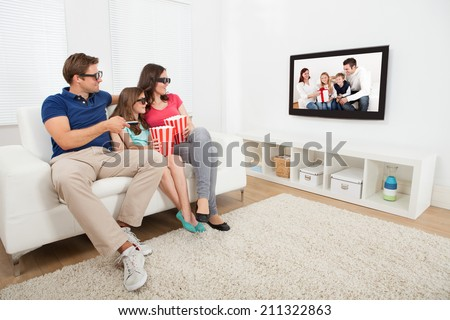 Full length of family watching 3D movie on television while having popcorn at home - stock photo