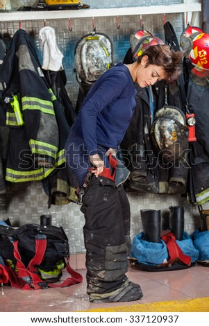 Full length of female firefighter wearing uniform at fire station - stock photo