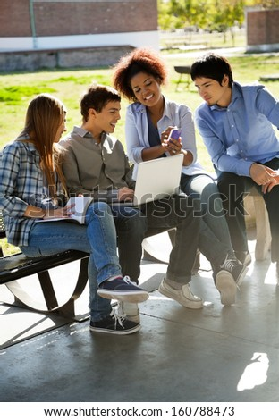 Full length of female student showing mobilephone to friends in college campus - stock photo