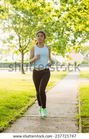 Full length of fit young woman jogging through the park - stock photo