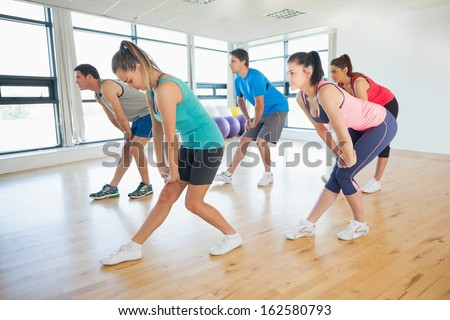 Full length of fitness class and instructor doing power fitness exercise in fitness studio - stock photo