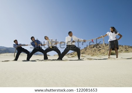 Full length of four multi ethnic businessmen playing tug of war against one woman in desert - stock photo
