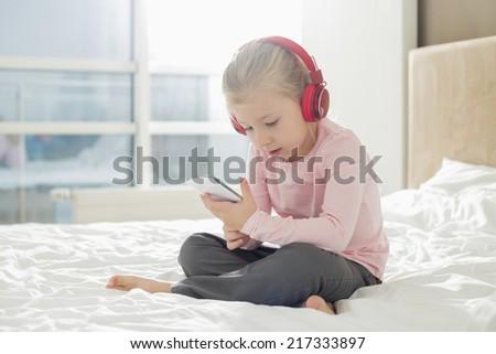 Full length of girl listening music on headphones in bedroom - stock photo