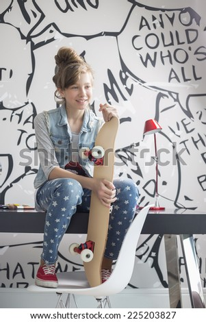 Full-length of girl with skateboard sitting on study table at home - stock photo