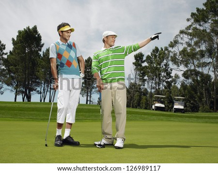 Full length of golfer pointing away to the ball for teammate - stock photo