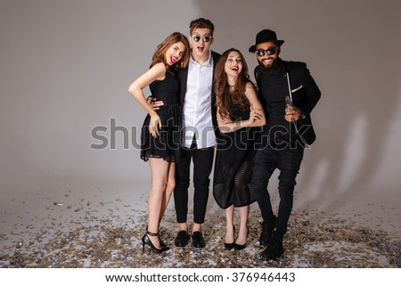 Full length of group of excited smiling young friends standing over white background - stock photo
