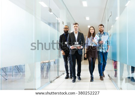Full length of group of happy young business people walking the corridor in office together - stock photo
