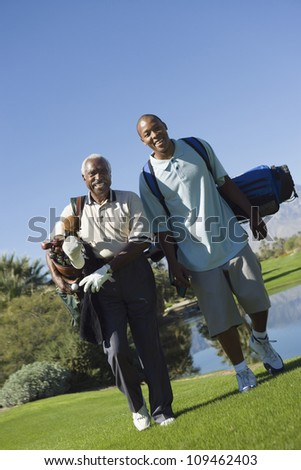 Full length of happy African American man with grandson carrying golf bags - stock photo