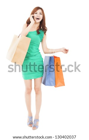 full length of Happy beautiful woman with shopping bags talking on the mobile phone - stock photo