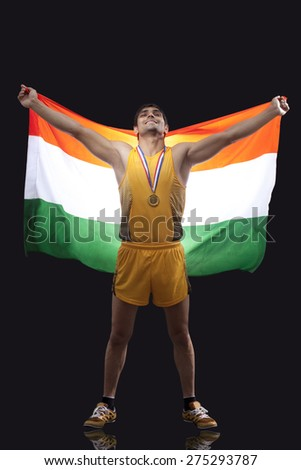 Full length of happy male medalist with Indian flag standing against black background - stock photo