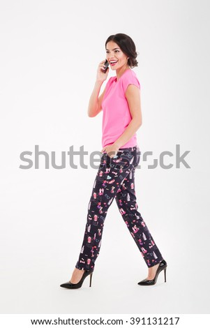 Full length of happy pretty young woman walking and talking on mobile phone over white background - stock photo