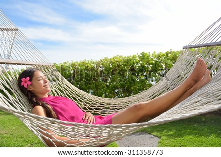 Full length of happy relaxed young woman lying on hammock. Smiling mixed race Asian / Caucasian female is in dress. She is enjoying sunlight in park. - stock photo