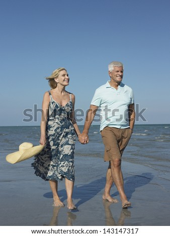 Full length of happy senior couple holding hands and walking on tropical beach - stock photo
