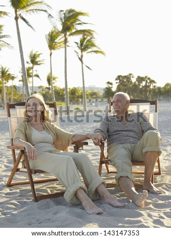 Full length of happy senior couple relaxing on deckchairs at tropical beach - stock photo