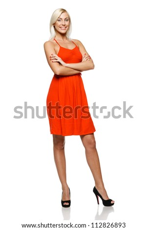 Full length of happy young woman standing with her hands folded against white background - stock photo