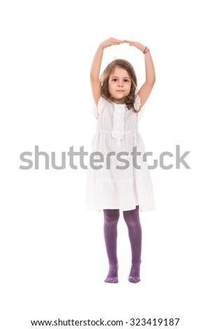 Full length of little ballerina girl dancing isolated on white background - stock photo