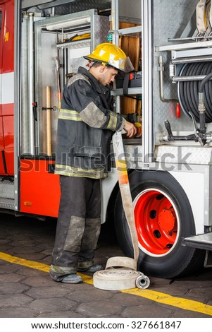 Full length of male firefighter fixing water hose in truck at fire station - stock photo