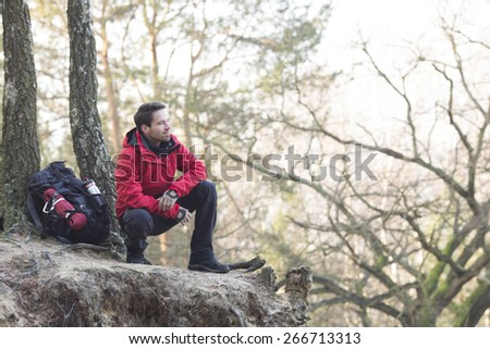 Full length of male hiker crouching on cliff in forest - stock photo