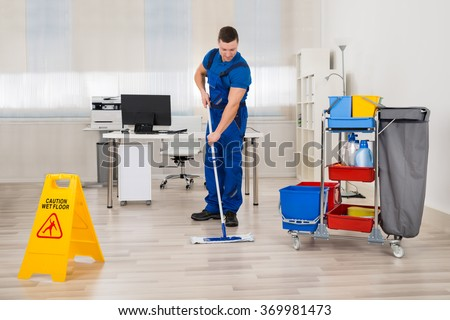Full length of male janitor mopping floor in office - stock photo