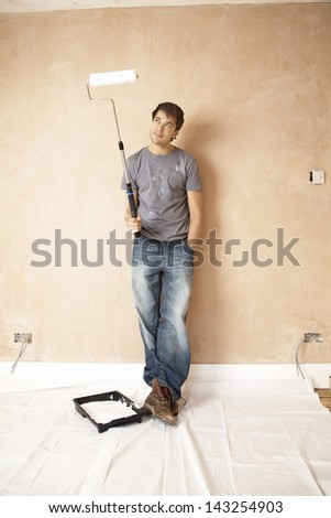 Full length of man looking at paint roller in unrenovated house - stock photo