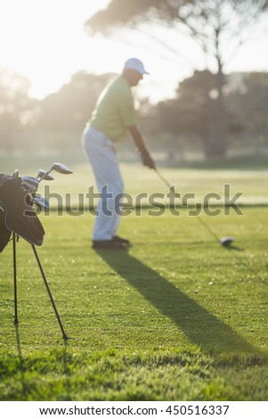 Full length of man playing golf while standing on field during sunny day - stock photo