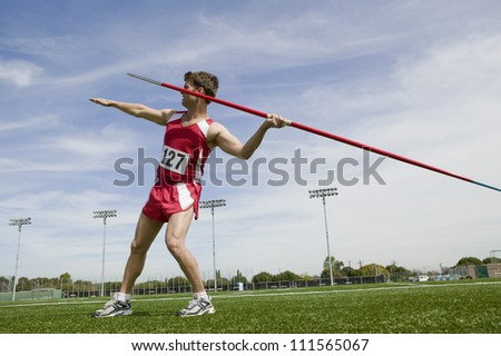 Full length of man with arm extended about to release javelin - stock photo