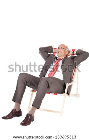 Full length of mature businessman with hands behind head relaxing on deck chair against white background - stock photo
