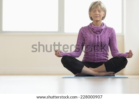 Full length of mature woman with eyes closed sitting in lotus position at home - stock photo