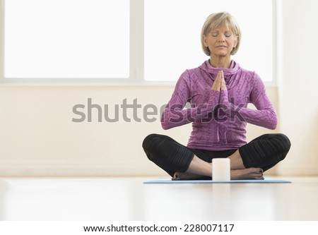 Full length of mature woman with hands clasped meditating at home - stock photo
