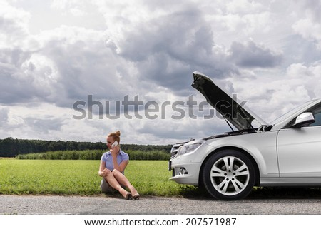 Full length of mid adult businesswoman on call while sitting beside broken down car at countryside - stock photo