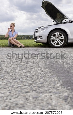 Full length of mid adult businesswoman using cell phone while sitting beside broken down car at countryside - stock photo
